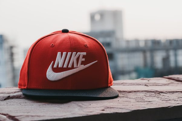 A red Nike cap on a ledge with a cityscape in the background