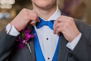 Man fixing his bowtie on his suit, with a flower on the jacket.